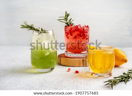 Three colorful summer cocktails in glasses on  white table. Assortment of fresh  summer drinks. Red sangria cocktails, orange punch cocktail, margarita cocktail, tropical mule.