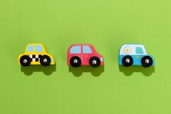 Three colorful wooden toy cars on green background placed neatly in a row in the center with drop shadows and copy space