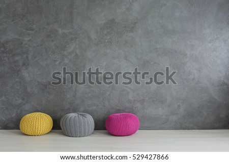 Three colorful wool poufs in concrete wall interior