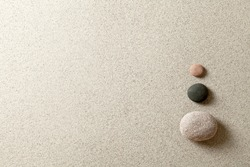 Three colorful zen stones at right side of sand background