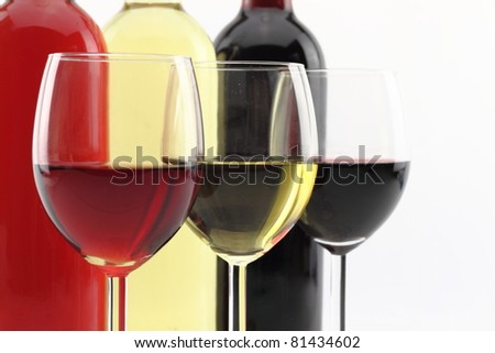 Three colors of wine in bottles and glasses - stock photo