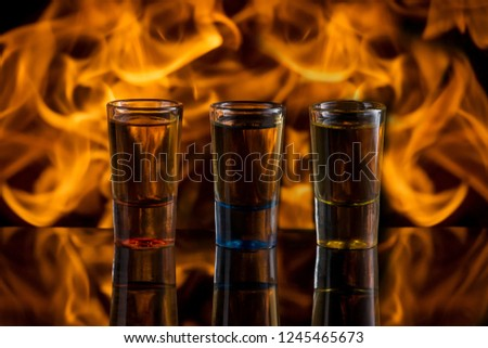 Three colour cocktails against fire with reflexion
