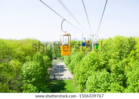 Three colourful cabins on rope in the city park. Panorama of cablecars - electric cabin transport. #1506339767