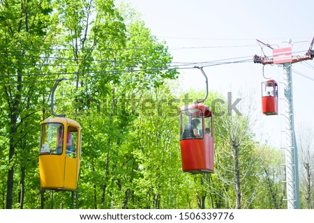 Three colourful cabins on rope in the city park. Panorama of cablecars - electric cabin transport. #1506339776