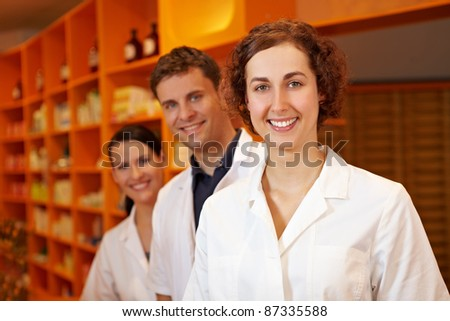 Three competent pharmacists smiling in a pharmacy