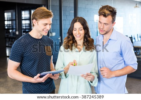 Three confident colleagues discussing in office with documents and tablet #387245389