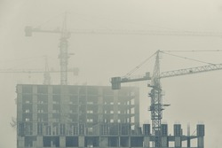 Three construction cranes protruding from the fog. Silhouette of view. High rise building under construction. Urban landscape with low cloud and smog. Monochrome.