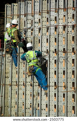 Three construction workers together on a high wall