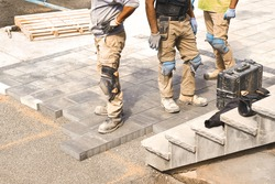 Three construction workers working on landscaping construction site, laying paving driveway stones slabs for quality garden patio stonework, home renovation project. Prospective view of man onsite job
