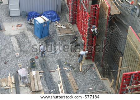 Three construction workers working on laying a foundation. in Providence, Rhode Island. - stock photo