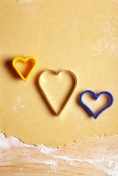 Three cookie cutters on dough with a heart shape