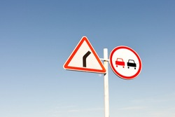 Three-cornered right turn sign on a highway in Russia. Road sign. Prohibitory sign. No overtaking. Overtaking is forbidden in suburban highway.