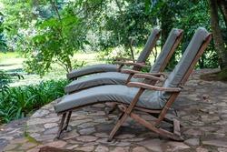 Three cozy sun loungers on the tropical garden terrace near lake. Tanzania, east Africa, close up