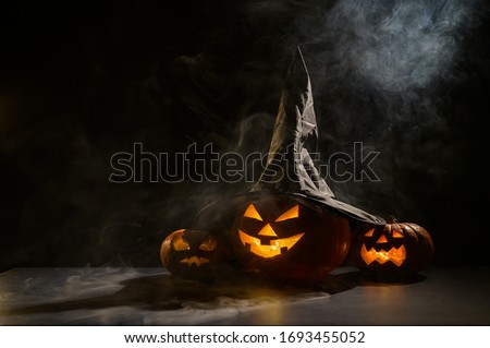 Three creepy Halloween grinning pumpkins glow in the dark among the fog. jack-o-lantern in a witch hat on a black background in smoke.