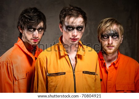 Three criminals in orange uniforms indoors