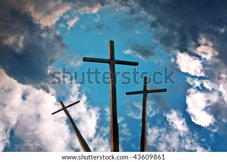 Three crosses above blue sky with clouds