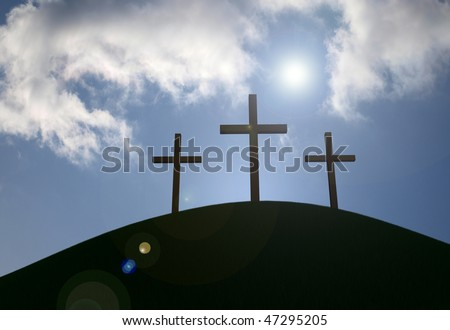 Three crosses on a grassy hill with sun-flare and clouds.
