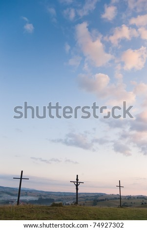 three crosses on sky with clouds and village on hills