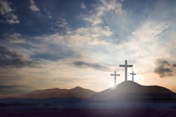 Three crosses on the mountain Jesus Christ with a sunset background