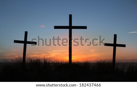 Three crosses with a light clouded sunset behind them