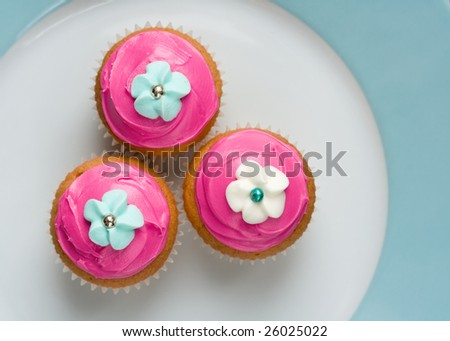 Three cupcakes on a plate - stock photo