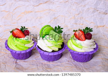 Three cupcakes with whipped cream, chocolate bar, strawberry ,decorated macaroons on crumpled paper. Picture for a menu or a confectionery catalog. with space for text.