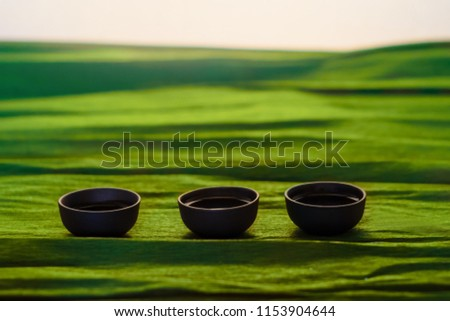 Three cups of ceramics on the green background, close view #1153904644
