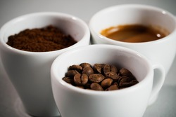 Three cups: with coffee beans, with ground coffee and with espresso