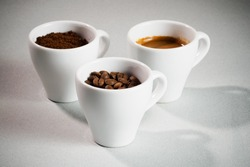 Three cups: with coffee beans, with ground coffee and with freshly brewed espresso