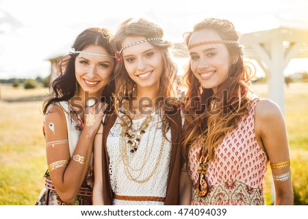 Three cute beautiful hippie girl in the setting sun, outdoors, the best of friends smiling and having fun, makeup, long hair, feathers in their hair, bracelets, flash tattoo, indie, Bohemia boho style #474094039