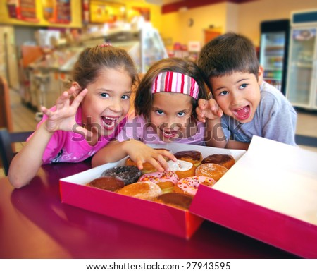 Three cute children eating donuts
