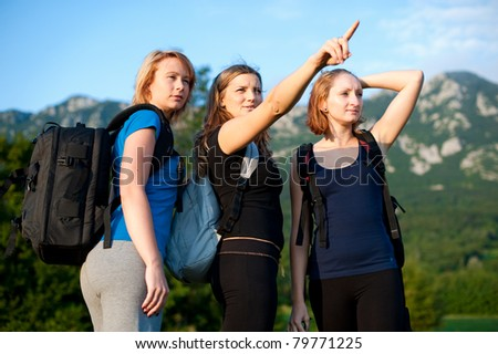 Three cute girls on a hike in nature - three women with backpacks on a trip