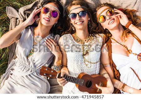 Three cute hippie girl lying on the plaid outdoors, best friends having fun and laughing, play ukulele, sunglasses, feathers in their hair, bracelets, flash tattoo, indie, Bohemia, boho style top view #471945857