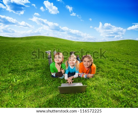 three cute kids laying with laptop on green grass in the park