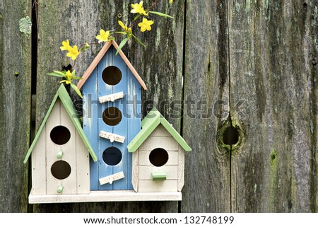 Three cute little birdhouses on rustic wooden fence with yellow flowers on them