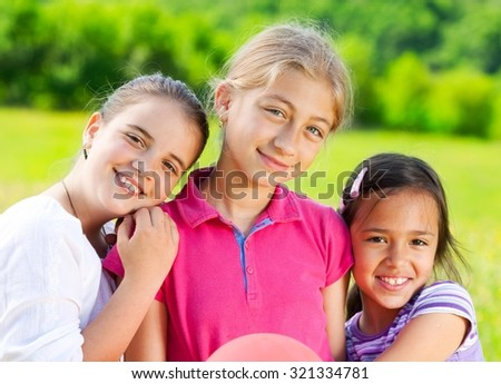 Three cute little girls standing in the meadow holding balloons. Elementary age. #321334781