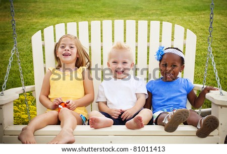 Three cute little kids sitting together on a porch swing
