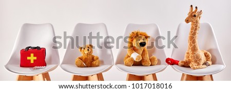 Three cute stuffed animal toys on chairs in the waiting room of a modern hospital or health center for children #1017018016