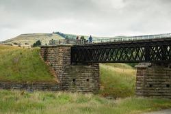 Three cyclists on historic stone bridge over the Cap Burn at Tiroiti, Otago Central Rail Trail, New Zealand