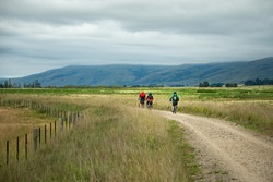 Three cyclists riding the Otago Central Rail Trail with heavy clouds over the mountain ranges, South Island