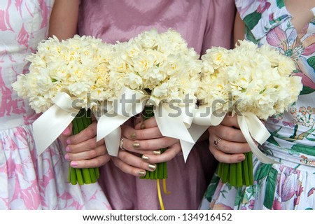 three daffodil wedding bouquets held by bridesmaids in vintage dresses