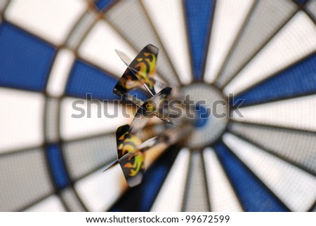 three darts at dart game just hit the bulls-eye in