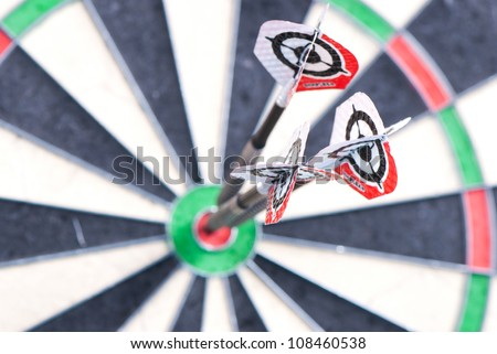 Three darts in bulls eye of dartboard with shallow depth of field concept for hitting target. Focus is on the ends of darts.