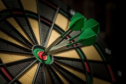 Three darts in the centre of a dartboard (bullseye). Success concept