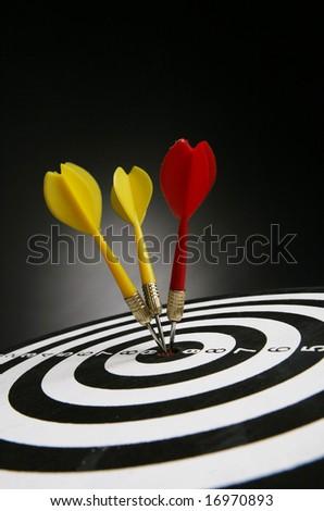 Three darts on bull's eye of a dart board