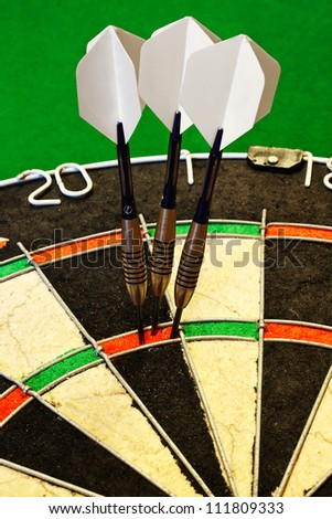 Three darts successfully scoring one hundred and eighty in a dartboard