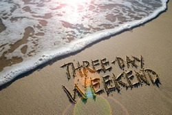Three-Day Weekend message handwritten on smooth sand beach with lens flare above an incoming wave