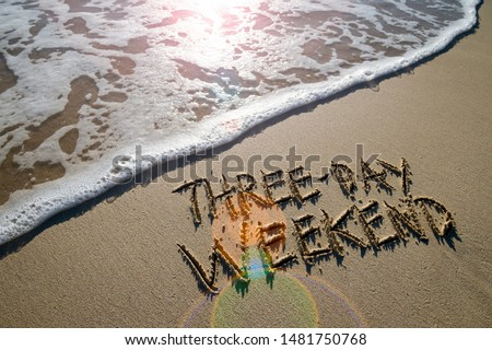 Three-Day Weekend message handwritten on smooth sand beach with lens flare above an incoming wave Stockfoto ©