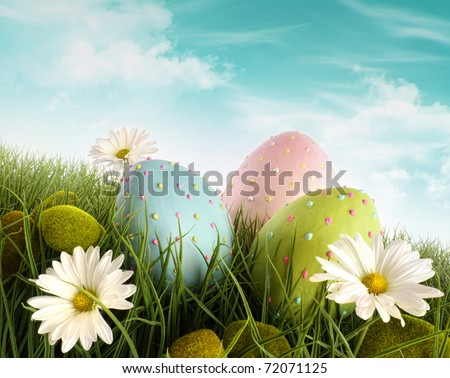 Three decorated easter eggs in the grass with daisies