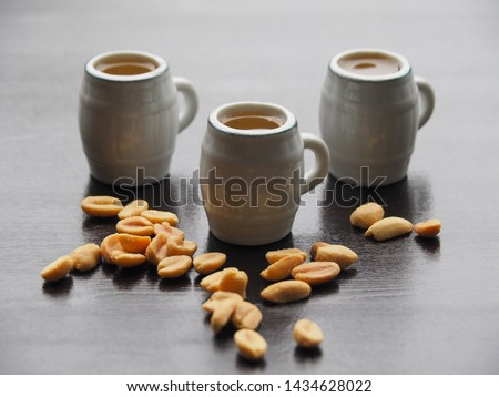 Three decorative beer mugs with light beer and salted peanuts are on the dark wooden table. Simple and original picture is with light beer mugs and nuts on a dark background.